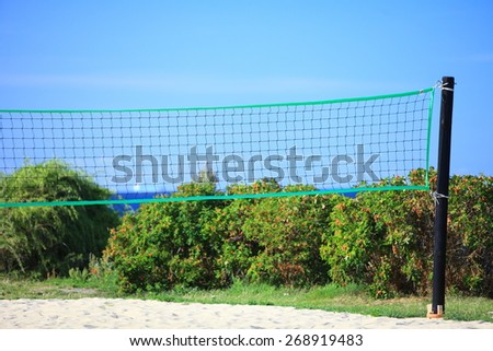 volleyball green net and playing court outdoor sea in the background. Sports concepts - stock photo