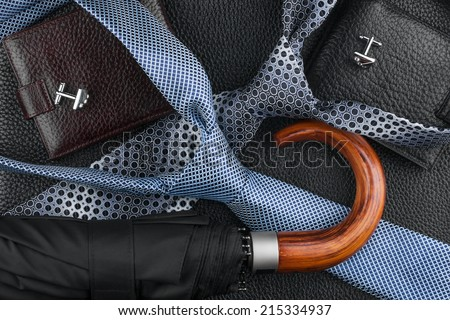 Wallet, tie, cufflinks, umbrella lying on the skin, can be used as background - stock photo
