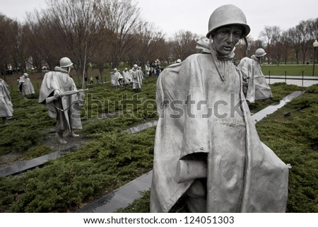 WASHINGTON, D.C. - MARCH 31: Statues representing American soldiers stand quietly at the Korean War Memorial during the Cherry Blossom Festival on March 31, 2011 in Washington, D.C. - stock photo