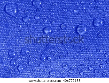 water drops on the umbrella fabric macro - stock photo