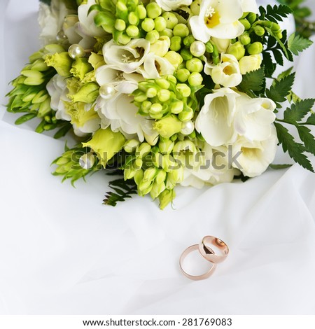 wedding bouquet and rings on white background - stock photo