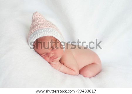 2 week old newborn girl wearing a pink, crocheted pixie hat sleeping on a white blanket. - stock photo