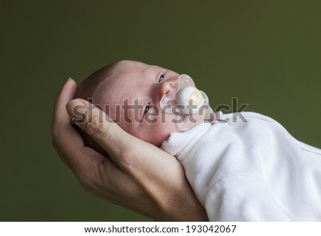3 weeks old european baby boy in his father's hand - stock photo