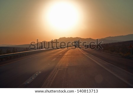 18-wheeler semi-trucks at sunset hit the highway driving down Interstate Highway 15 between Los Angeles and Las Vegas Nevada. - stock photo