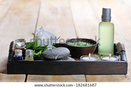 white flower with candle and massage stones on platter  - stock photo
