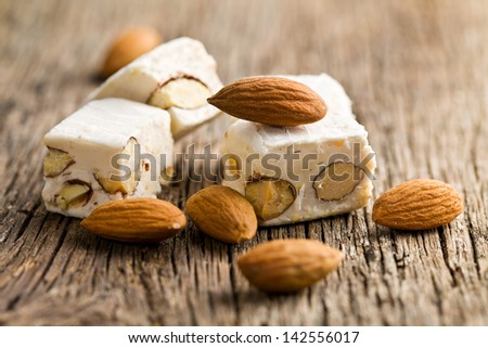 white nougat with almonds on wooden table - stock photo