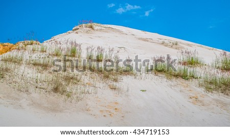 White sand hill against the blue sky. - stock photo