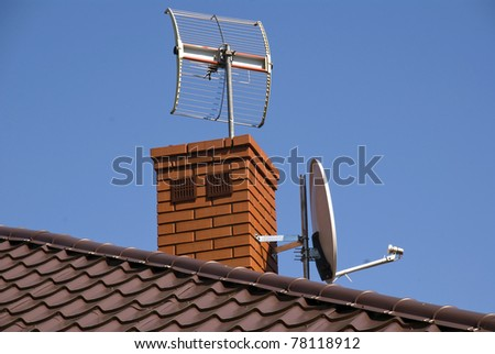 White satellite dish on brown roof - stock photo