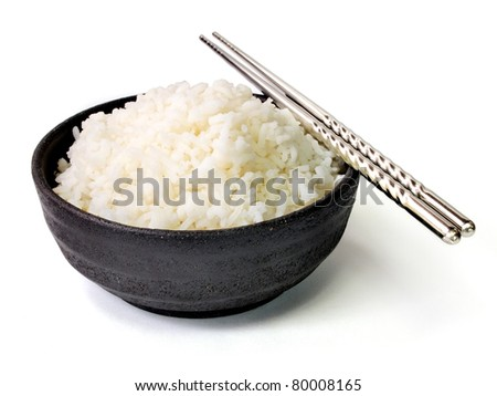 White steamed jasmine rice in black ceramic bowl with silver chopsticks - stock photo