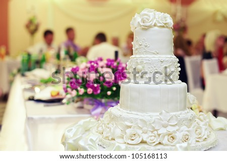 white wedding cake on restaurant interior background - stock photo