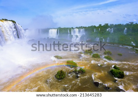 White whipped foam of water and a thin mist over the water.  Magnificent rainbow shines in the mist. The most high-water waterfall in the world - Iguazu. The Brazilian side of the park.  - stock photo