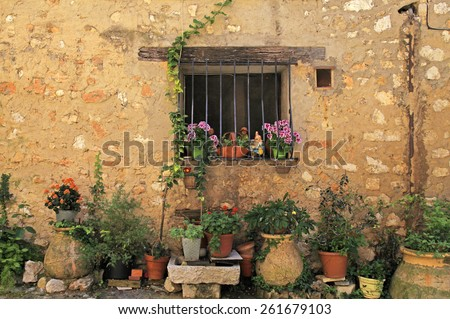 window in stone medieval village rural house with many flower pots, Provence, France. - stock photo