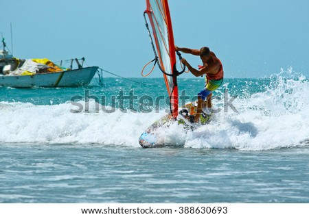 Windsurfing surfing in the waves near old boat - stock photo