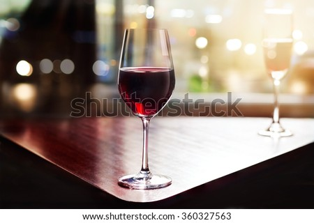 wine glass in entertaining room among sunset window background - stock photo
