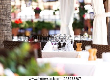 4 wine glasses on table of street outdoor restaurant - stock photo