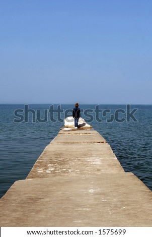 Woman alone on the pier on a beautiful calm day - stock photo