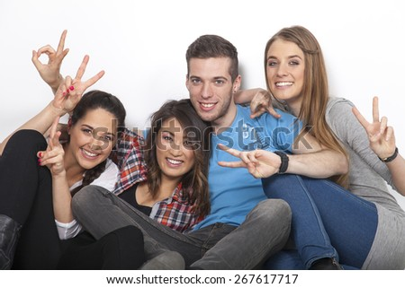 3 woman and 1 man showing victory sign with their hands - stock photo