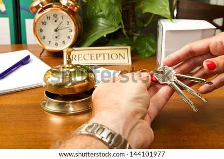 woman at the reception of a hotel checking in - stock photo