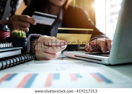Woman hands using laptop and holding credit card with digital layer effect diagram as Online shopping concept in morning light.  - stock photo
