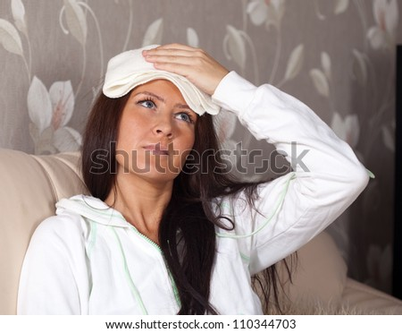 woman having  headache holding towel on her head - stock photo