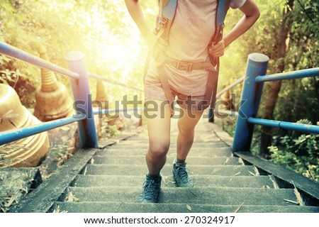 woman hiker climbing stairs at mountain peak  - stock photo