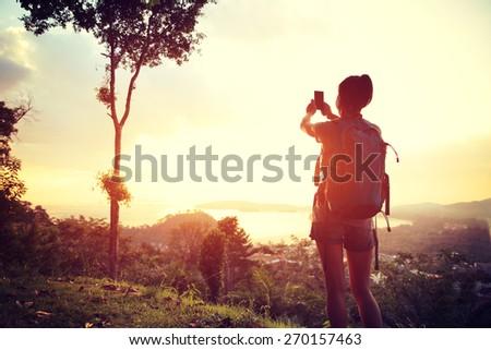 woman hiker taking photo at mountain peak  - stock photo