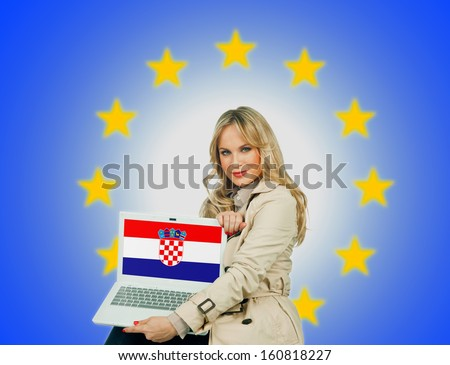 woman holding laptop with croatian flag on the screen and european union stars in the background - stock photo