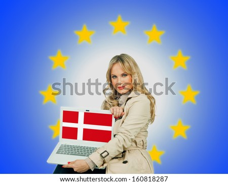 woman holding laptop with denmark flag on the screen and european union stars in the background - stock photo