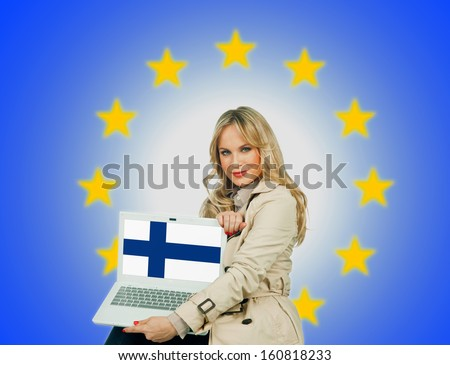 woman holding laptop with finland flag on the screen and european union stars in the background - stock photo
