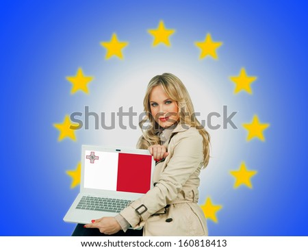 woman holding laptop with malta flag on the screen and european union stars in the background - stock photo