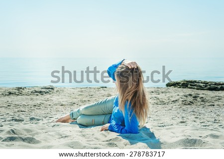 woman in a blue blouse and jeans lying on the sand, basking in the sun and looking at the blue sea - stock photo