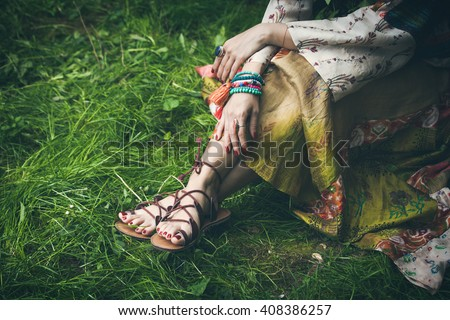 woman legs  on grass in strap flat sandals and boho style silky  dress  with lot of bracelets on hands  - stock photo