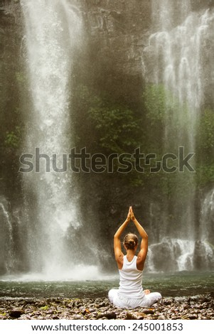 woman meditating in lotus position while doing yoga between waterfalls - stock photo