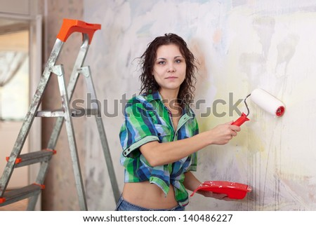 woman paints wall with roller at home - stock photo