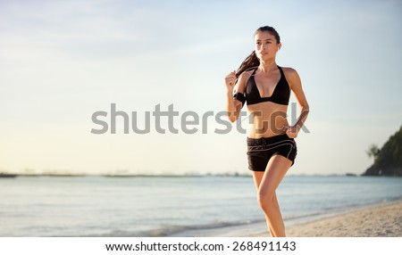 Woman runner jogging on beach - stock photo