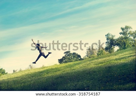 woman running and jumping funny relax on green grass and flower field   - stock photo