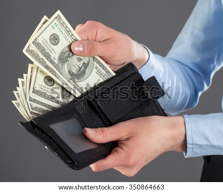 : Woman's hands taking money out of leather wallet on dark background - stock photo