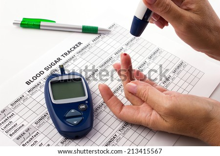 woman's hands testing for sugar level in blood, near lie glucometer, medicine form on white background - stock photo