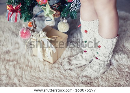 woman's leg under new year tree with christmas present - stock photo