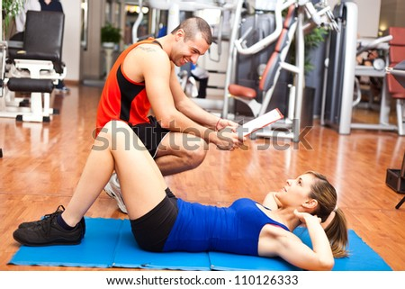Woman training abdominal on the floor in the gym with a personal trainer - stock photo