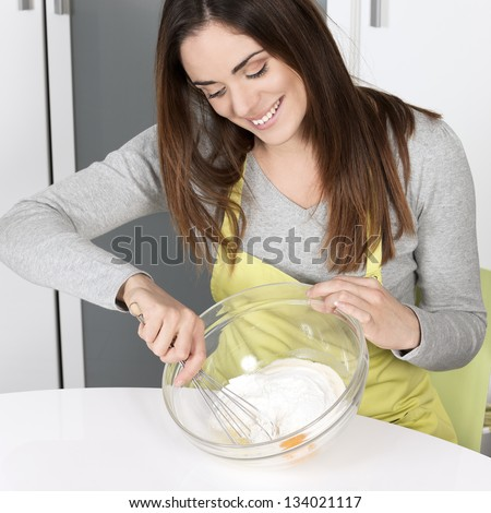 woman whisking batter in kitchen - stock photo