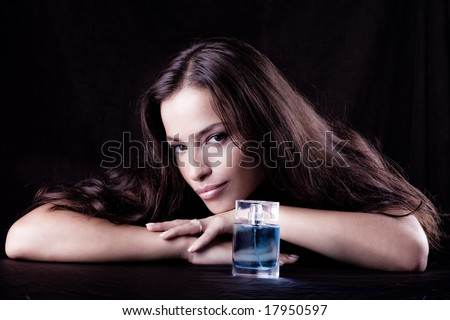 woman with bottle of perfume, studio dark background - stock photo