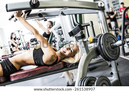 3 woman with long brunette hair sitting smiling face Portrait of three young adult Girls do exercise for legs and hands. in fitness gym on mirror with reflection and window background Group of people - stock photo