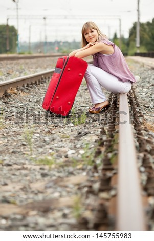 woman with luggage sitting on rail - stock photo