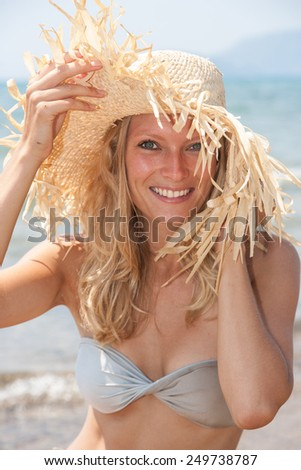 woman with straw hat on the beach - stock photo