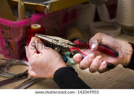 Woman working with pliers and other tools - stock photo