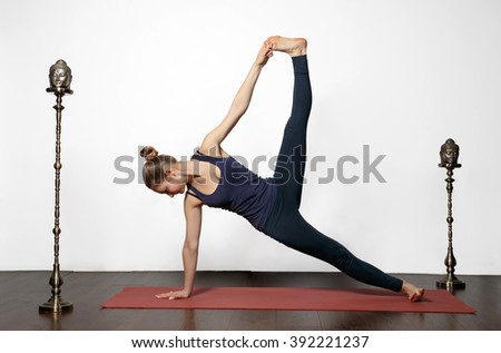 women are yoga exercises at home. She stands on a red yoga Mat leaning on one arm and a leg. the other foot she was holding up - stock photo