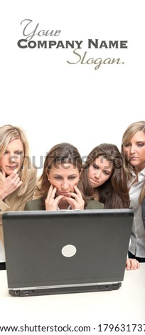 4 women with serious expressions around a desk with computer  - stock photo