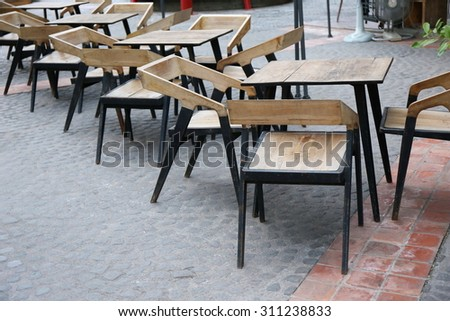 wood table, Europe cafe outdoor , ,wood tables and black chairs set up for lunch outside cafe, street side in Europe, leisure corner with wood chairs and table - stock photo