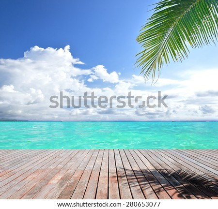 Wooden footbridge beside tropical sea - stock photo